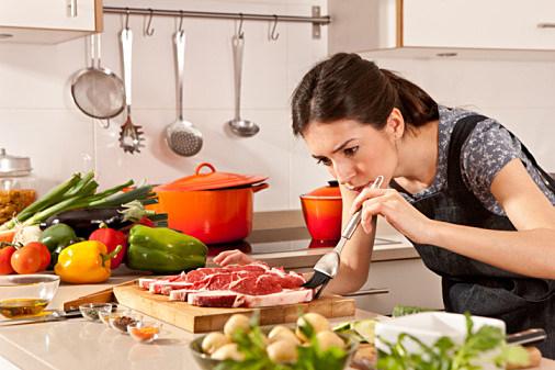 woman seasoning meat